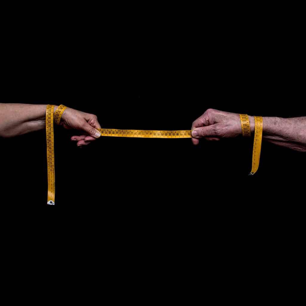Imagem com fundo preto de duas mãos segurando uma fita métrica na cor amarela.