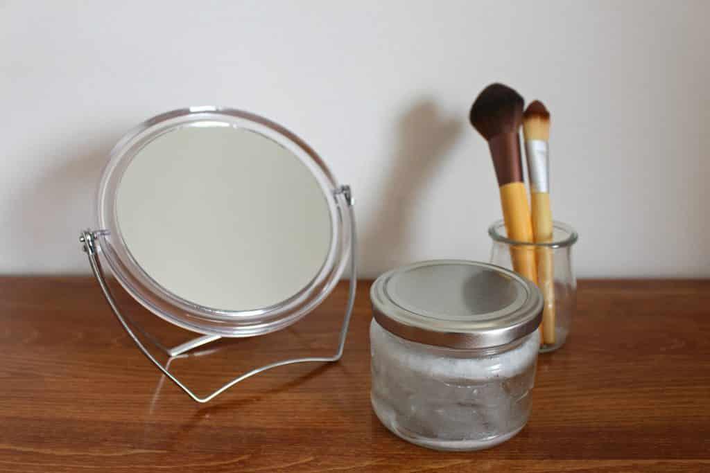 Imagem de um conjunto de espelho e pincéis para uso de maquiagem. Ao lado do kit um pequeno pote contendo um creme demaquilante natural.