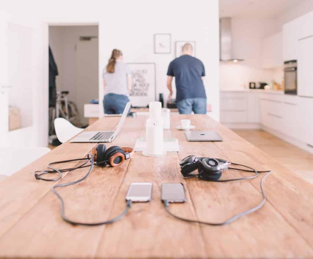 Homem e mulher em pé atrás de uma mesa com computadores, celulares e fones de ouvido.