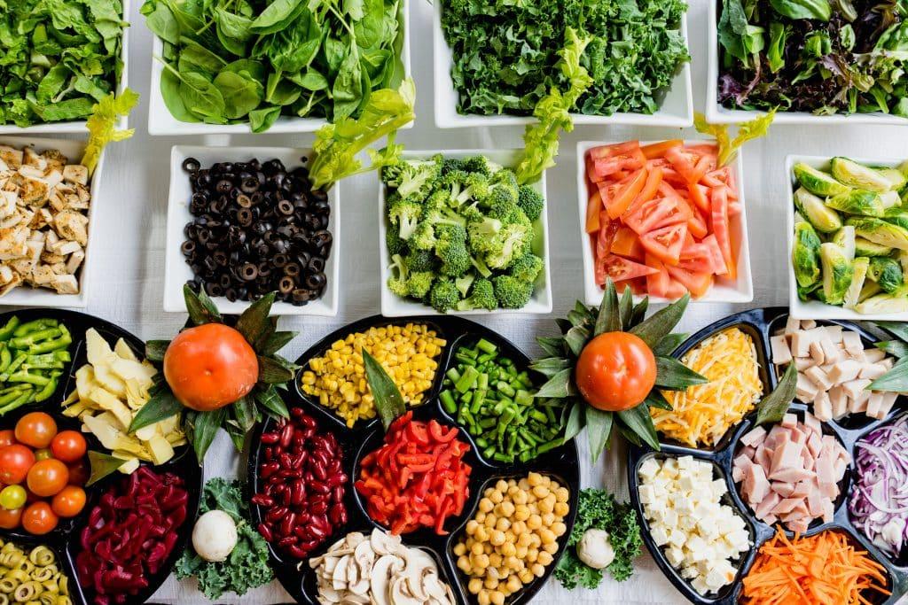 Mesa com diversos tipos de verduras e legumes dispostos em recipientes quadrados.