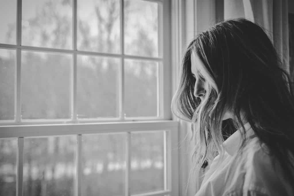 Mulher de cabelos lisos vista de perfil, olhando pela janela.