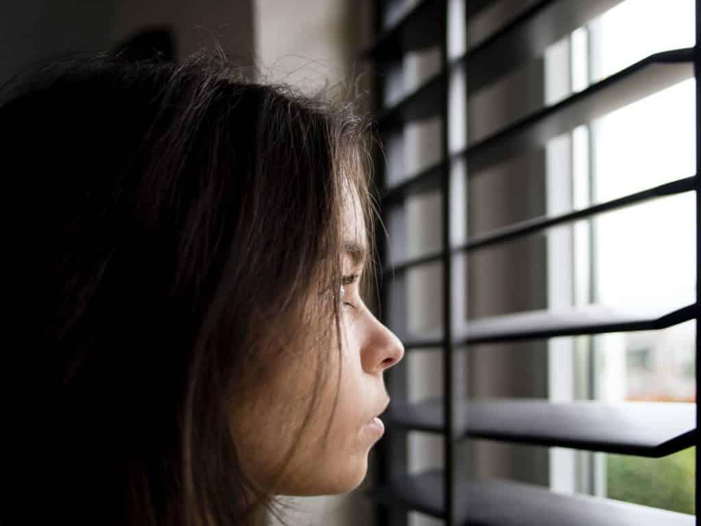 Mulher de frente para uma janela pensativa