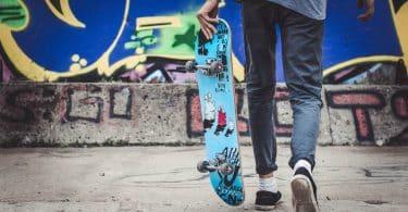 Adolescente segurando um skate enquanto anda