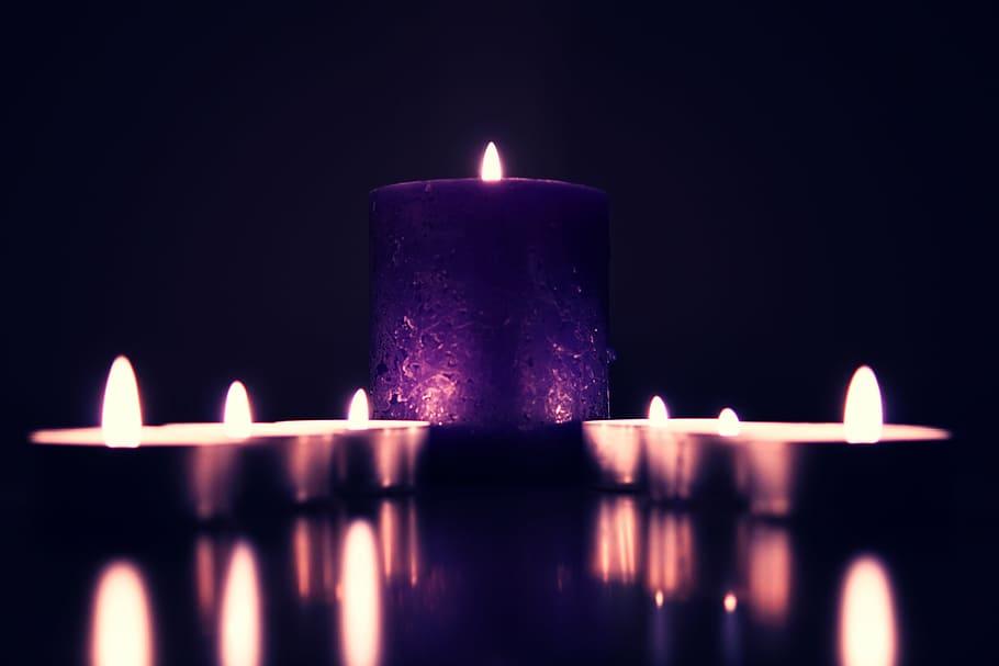 Seis velas pequenas, divididas em duas fileiras com três cada, trilhando o caminho até uma vela grande. Todas estão acesas.
