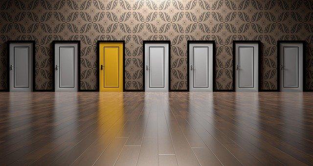 Sete portas idênticas lado a lado, seis delas são brancas, menos a terceira da esquerda para a direita, que é amarela.