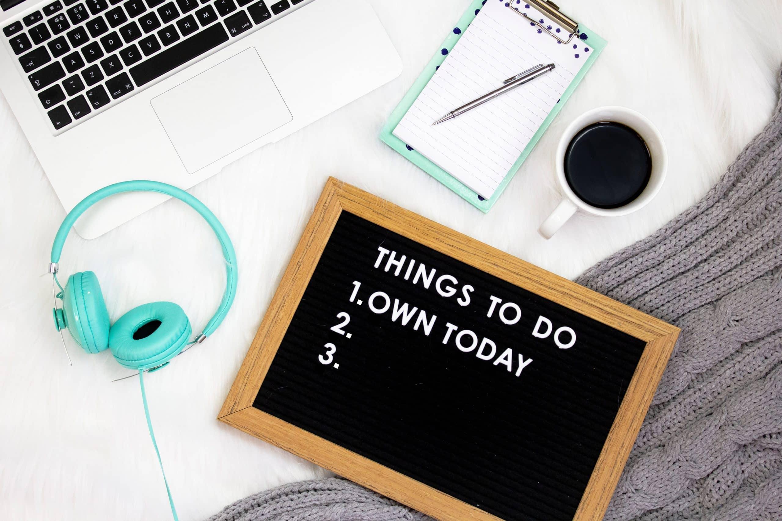 Notebook, fone de ouvido, caderno, xícara de café e plaquinha de lista vistos de cima em cima da cama