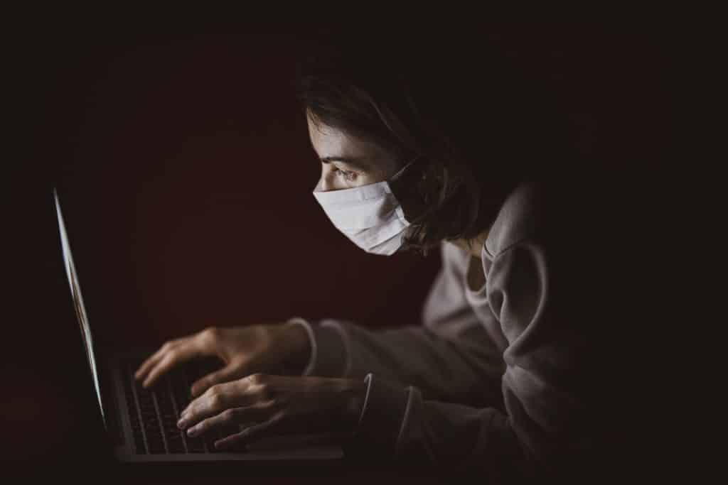 Mulher olhando para notebook com sua máscara de proteção