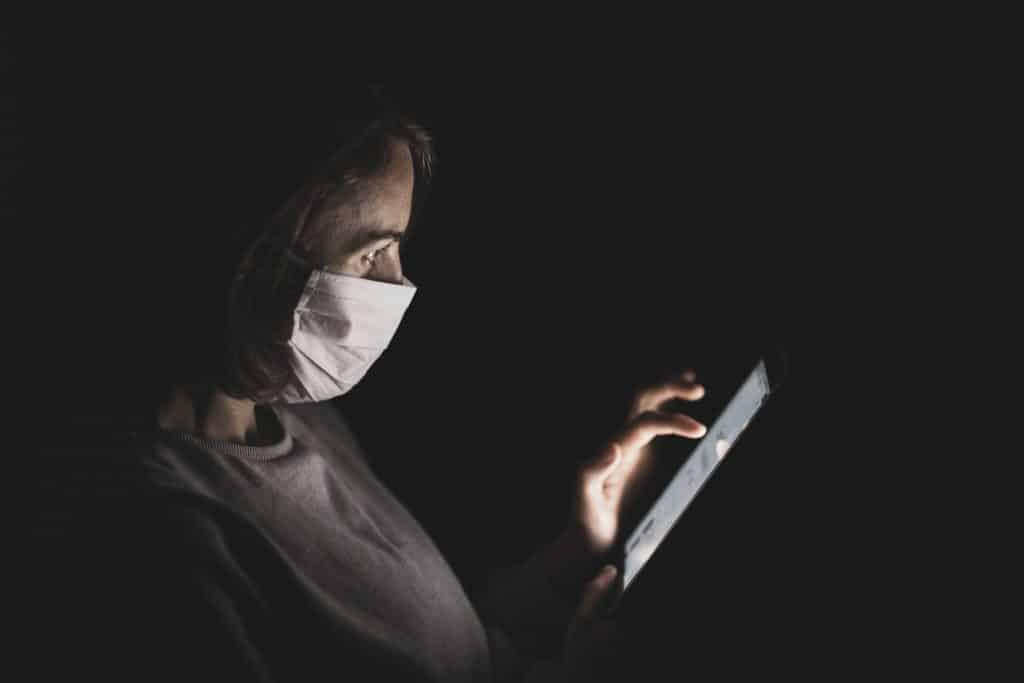 Mulher em um quarto escuro de máscara e usando o celular