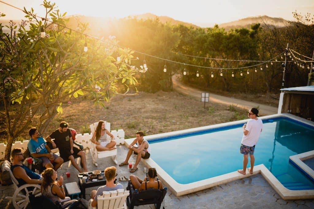 Amigos reunidos sentados em círculo ao lado de uma piscina.