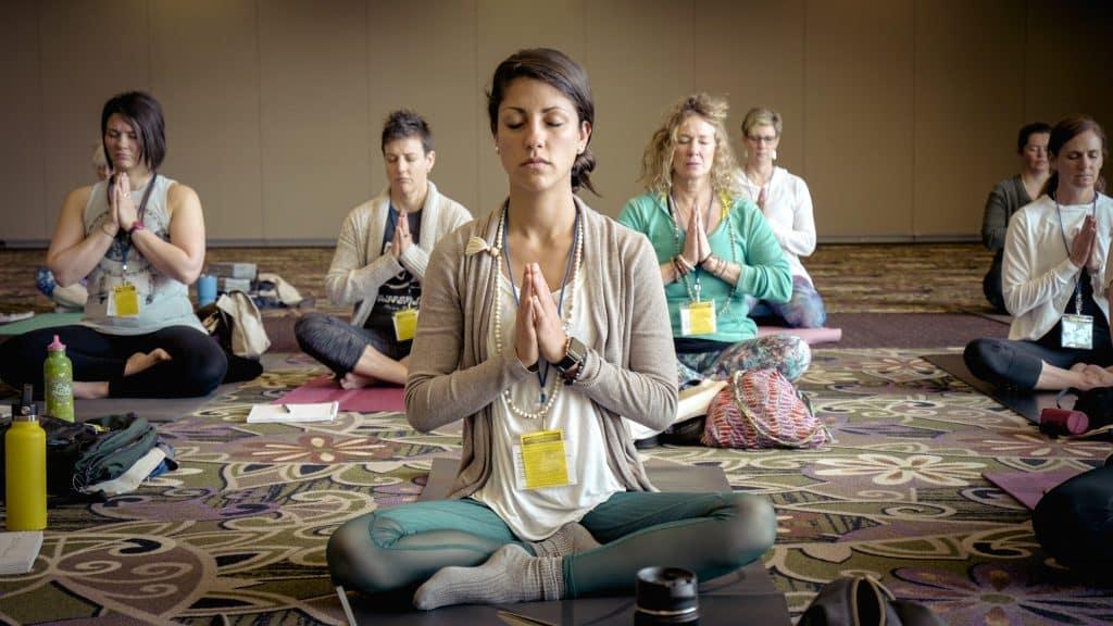 Pessoas sentadas no chão, de pernas cruzadas e olhos fechados, praticando Yoga.