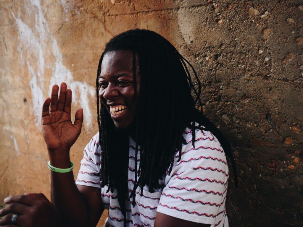 Homem agachado em uma parede sorrindo.