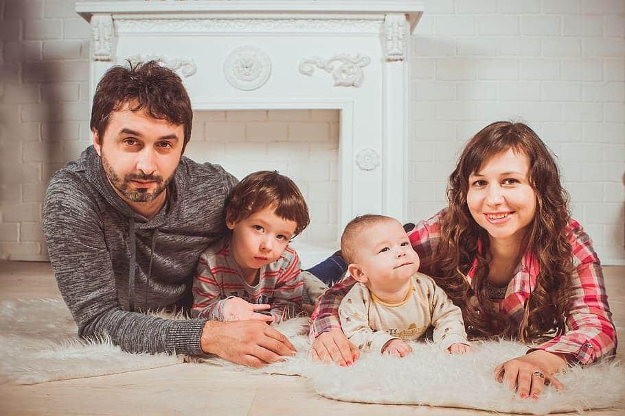 Família deitada de bruços no chão de uma sala. Um homem, um menino pequeno, um bebê e uma mulher.