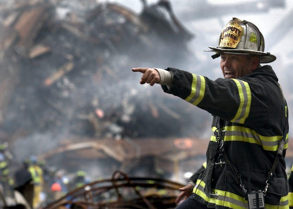 Bombeiro apontando para a frente em meio a um cenário de incêndio.