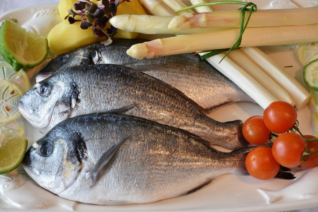 Imagem de três peixes crus separados para serem preparados em uma refeição. Temos ainda, tomates, limões, aspargos que farão parte da receita,