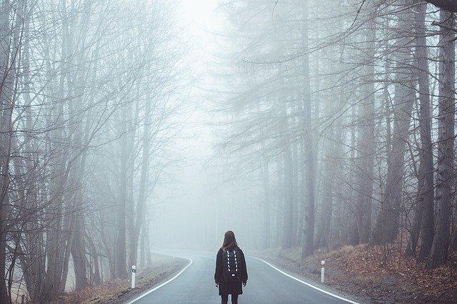 Mulher em pé no meio de rodovia com neblina e árvores dos dois lados