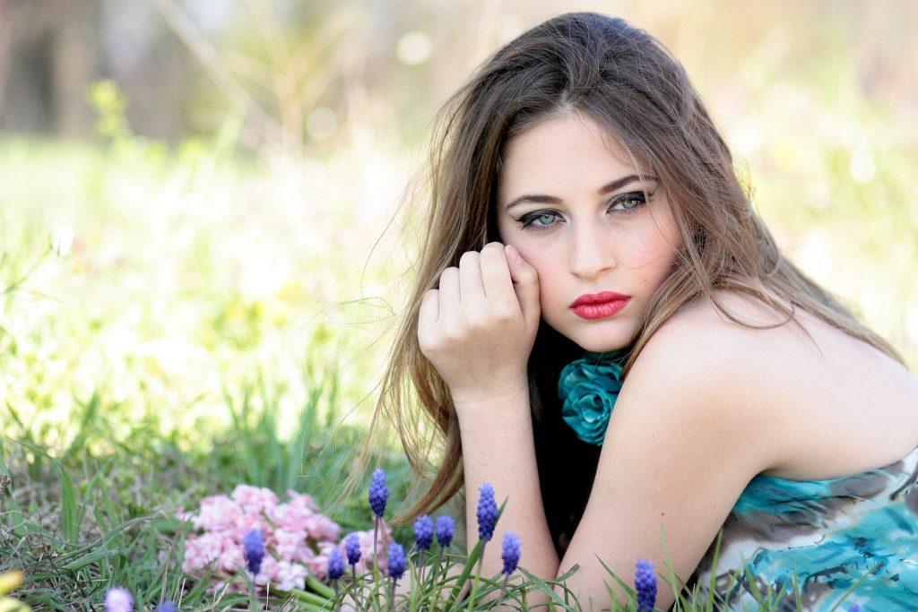 Imagem de uma linda mulher de olhos azuis, cabelos longos. Ela usa um batom vermelho e um vestido azul claro. Ela está deitada sobre um gramado com flores.