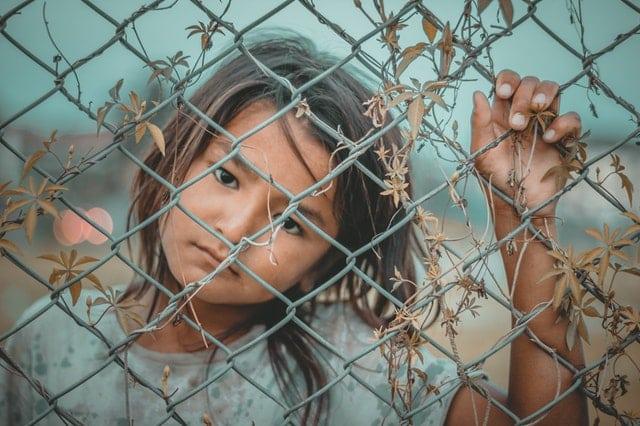 Garota vistas por tás de grade com mão apoiada e expressão triste