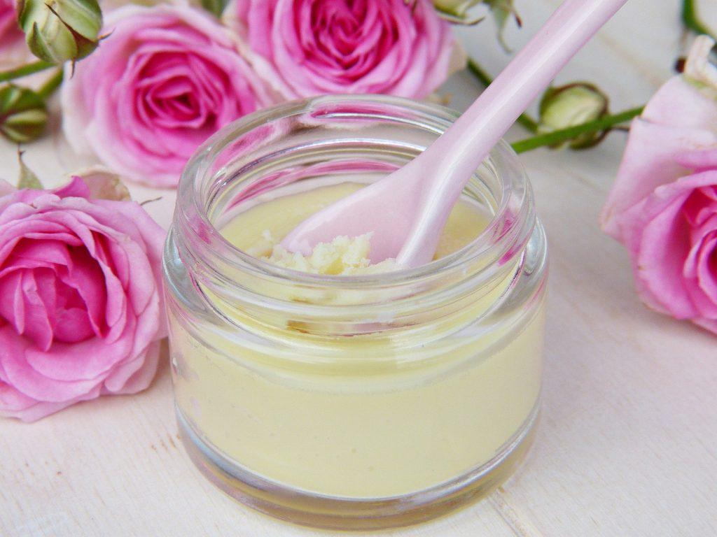 Imagem de um pote com cera natural para depilação. Atrás do pequeno pote de sera, rosas na cor rosa.