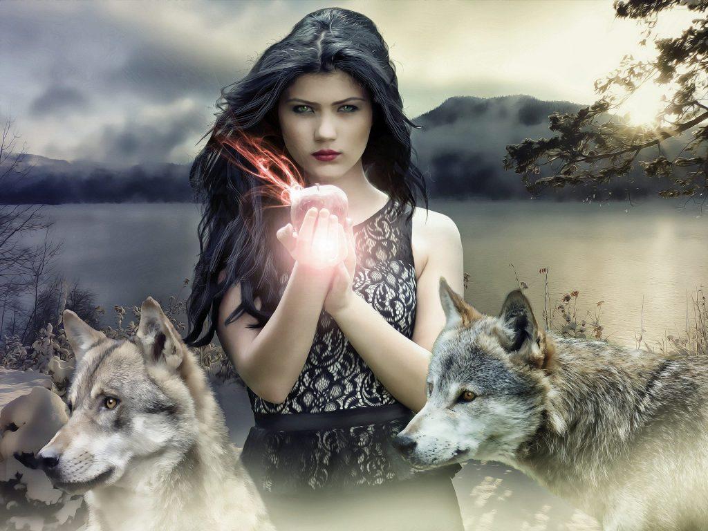 Imagem de uma mulher gótica, estilo bruxa. Ela tem cabelos longos pretos e segura entre as mãos uma maçã. Ao lado dela dois lobos.