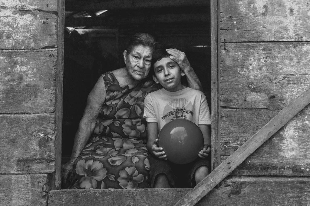 Imagem em preto e branco de uma janela de uma casa feita de madeira Na janela a imagem de uma vó enconstada em seu neto. O menino segura em suas mãos uma bola.