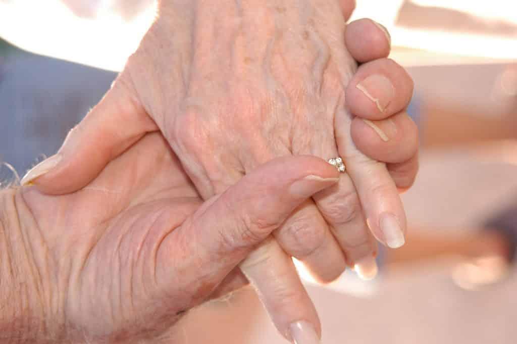 Imagem de duas mãos de pessoas idosas. A mão de um senhor segurando a mão de sua senhora.