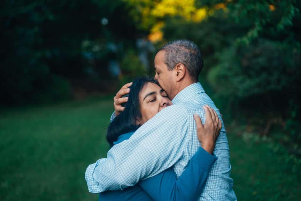 Homem e mulher se abraçando em um jardim
