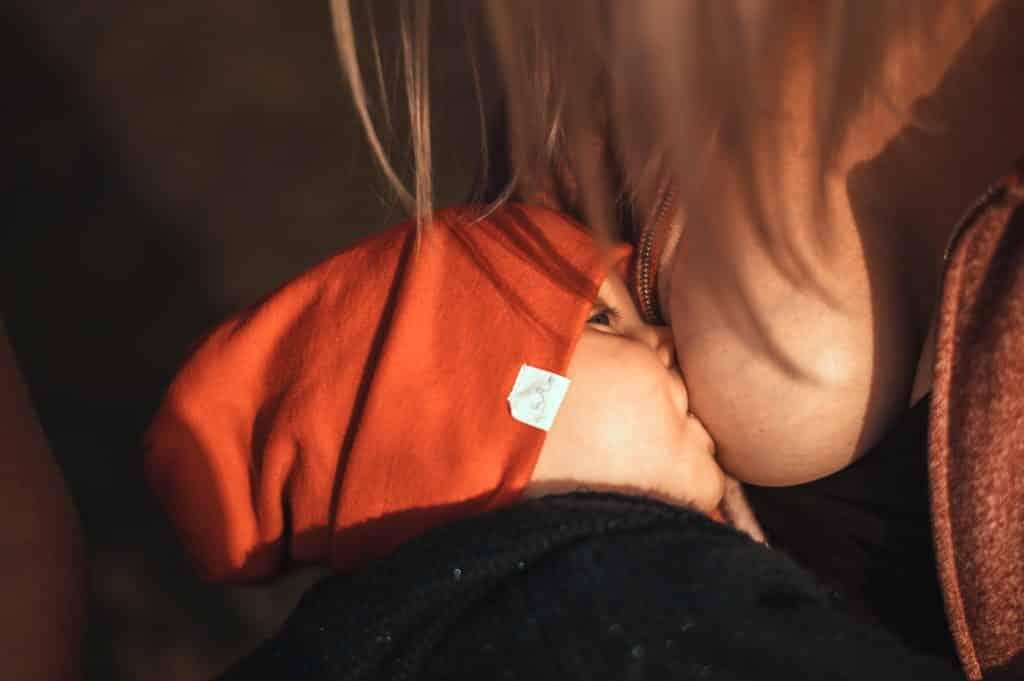 Mulher amamentando bebê, que usa uma touca.
