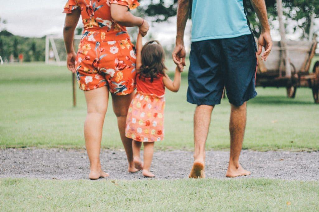 Pai e mão segurando mãos da filha pequana que está no meio deles, enquanto andam em um parque.