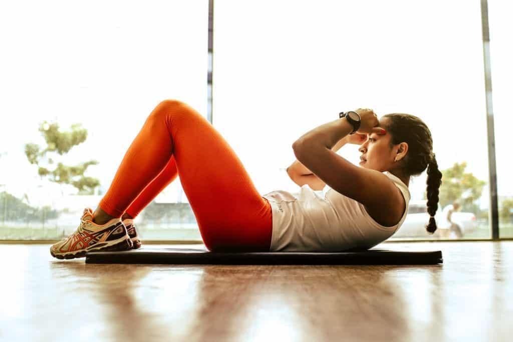 Mulher deitada no chão sobre um tapete de ginástica, fazendo abdominais.