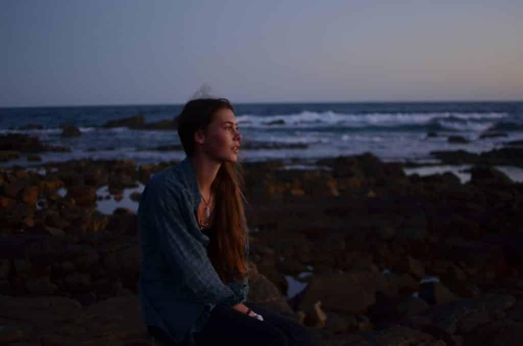 Mulher sentada em uma rocha perto do mar