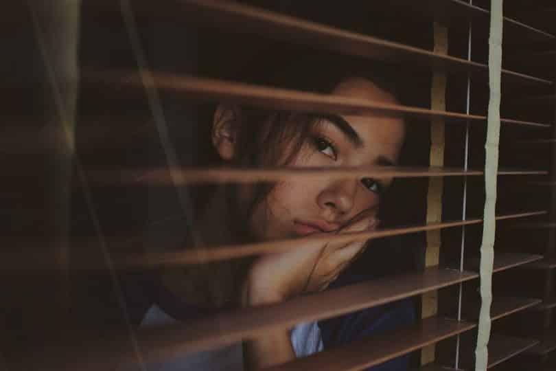 Mulher olhando através da janela com expressão de cansada e pensativa