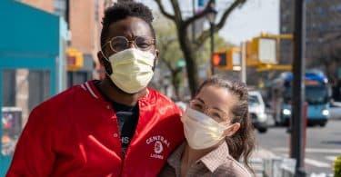 Casal na rua usando máscara de proteção