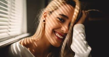 Mulher sorrindo apoiando sua mão na cabeça ao lado de uma janela