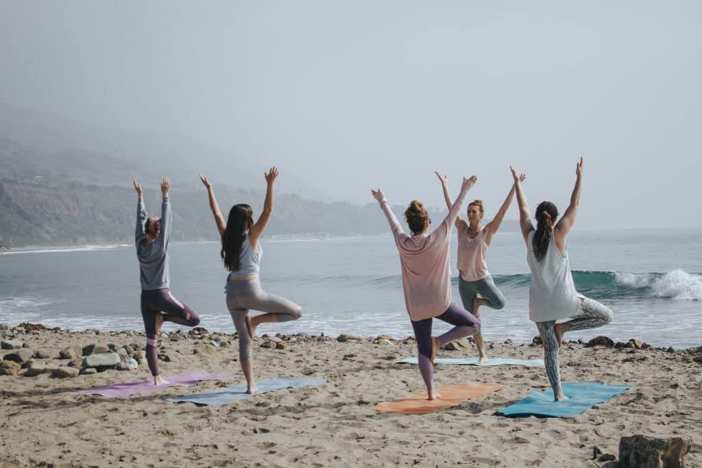 Pessoas em pé, com os braços para cima, fazendo aula de Yoga na praia.
