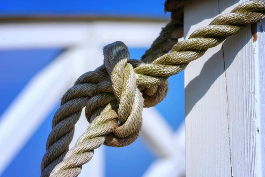 Imagem de uma corda bege com um nó. Ela está presa a uma madeira pintada na cor branca.