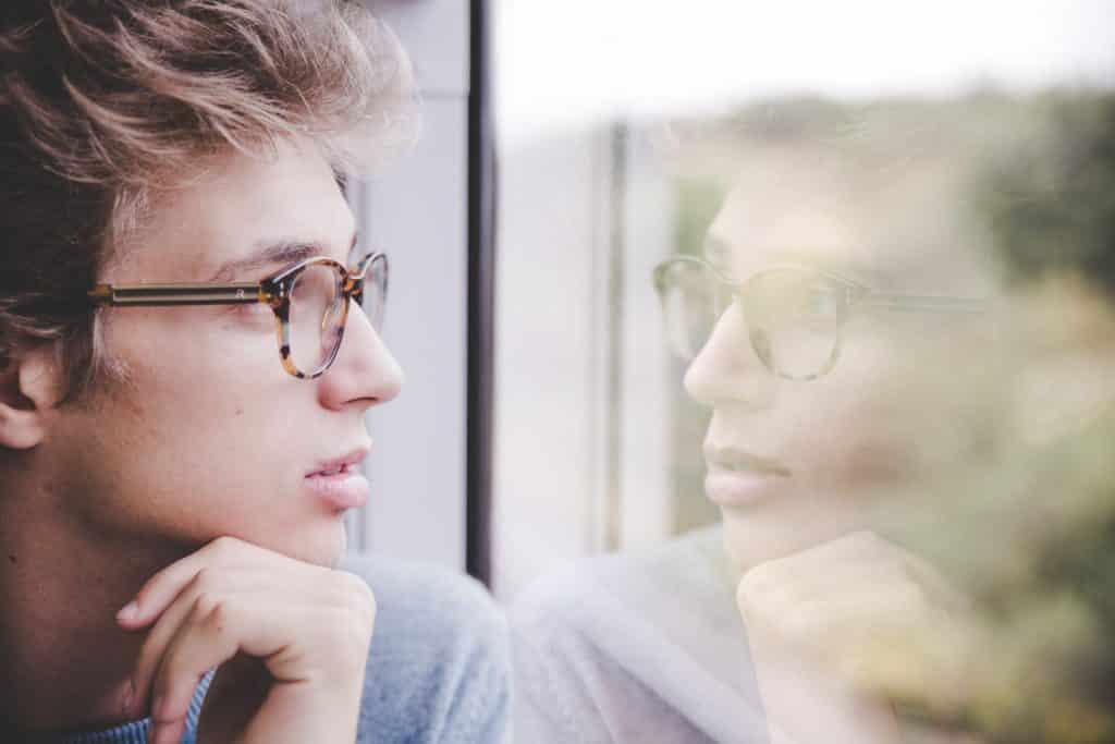 Homem pensativo ao lado de uma janela que mostra seu reflexo