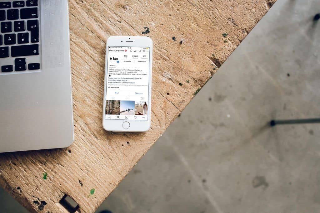Mesa de madeira com laptop e um celular