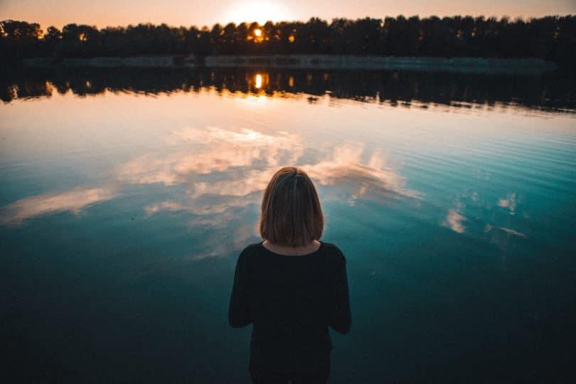 Mulher olhando para o mar refletindo o céu.