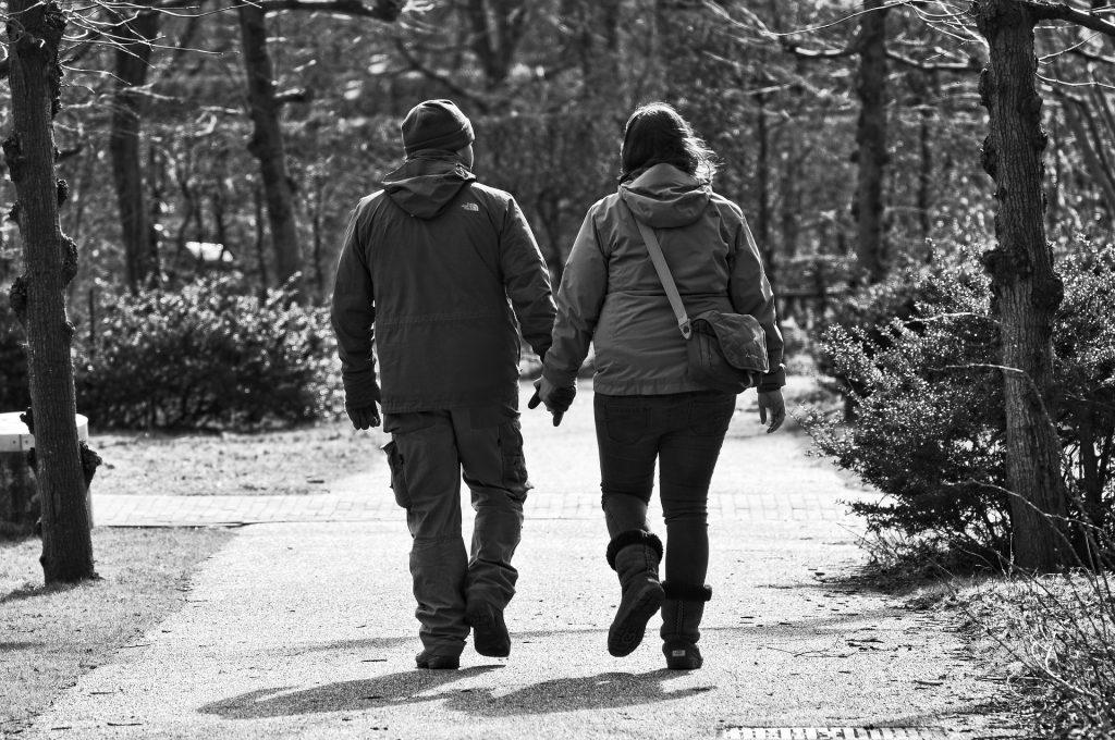 Imagem de um casal de meia idade vestidos com casados de frio. Eles estão de mãos dadas e caminham em um parque.