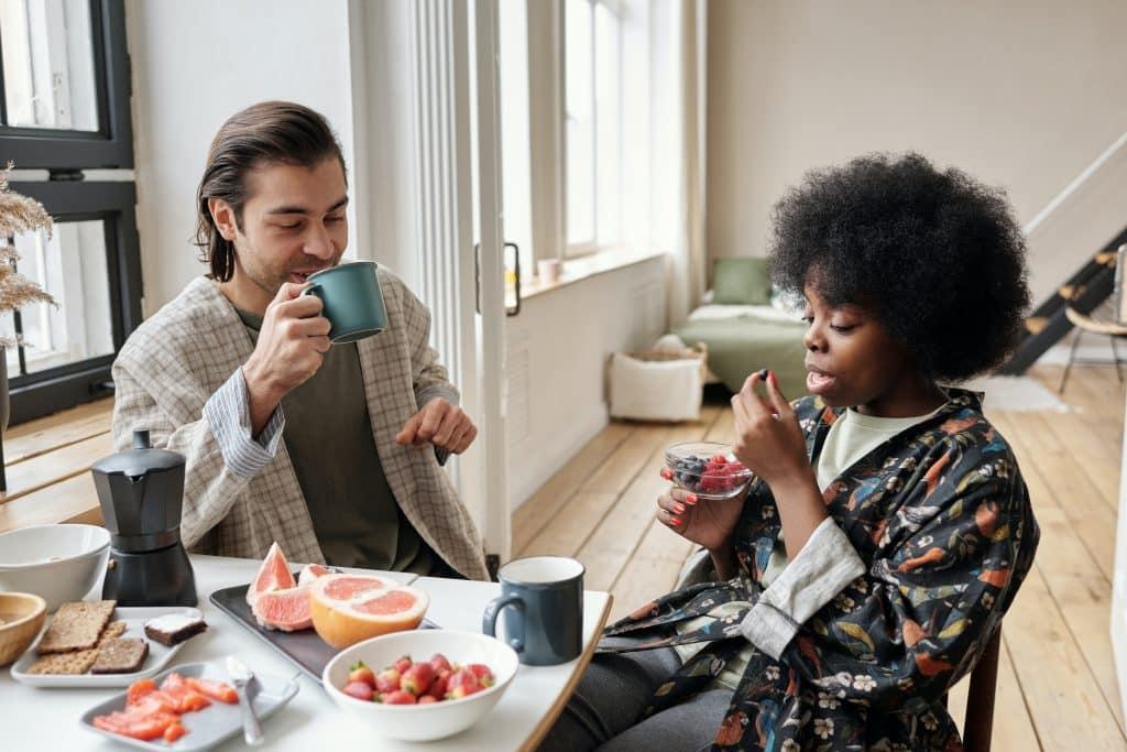 Homem e mulher sentados tomando café da manhã em uma mesa com frutas e canecas.