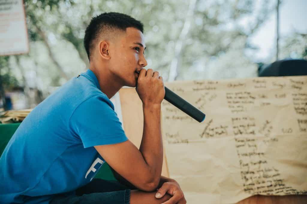 Homem jovem falando em microfone, segurando-o bem próximo de sua boca.