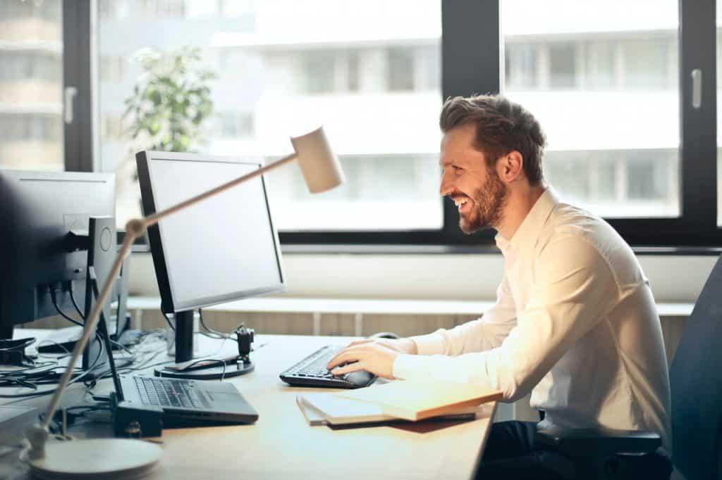 Homem em escritório, usando um computador.