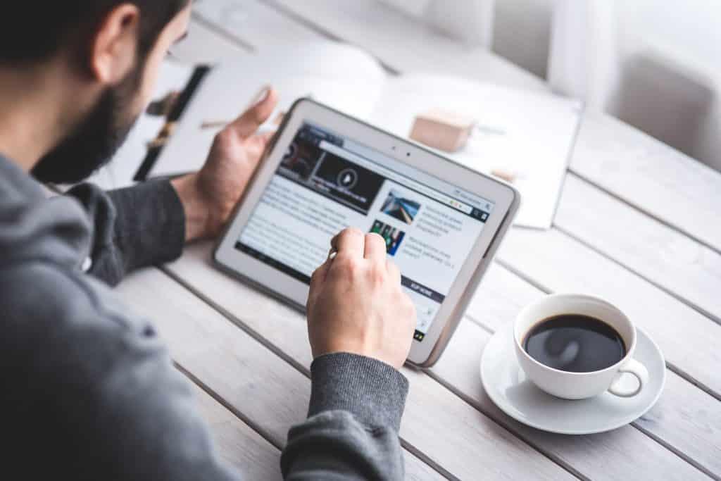 Homem estuda segurando um tablet sobre uma mesa com livros e uma xícara de café.