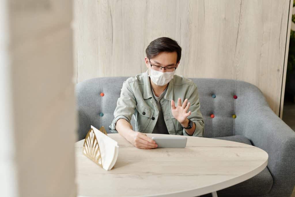 Homem usando máscara em casa, enquanto faz uma chamada de vídeo pelo seu celular.