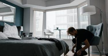 Homem em um quarto arrumado durante o dia, sentado em uma cadeira, amarrando os cadarços de sua bota.