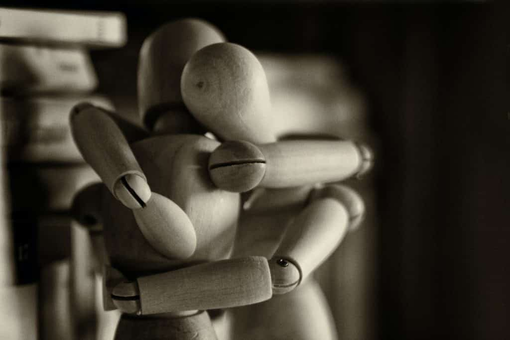 Dois bonecos de madeira usados para molde de desenho abraçados.