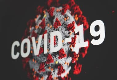 Vírus do coronavírus com letreiro grande escrito Covid-19.