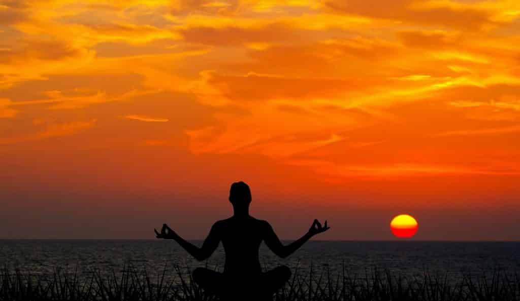 Imagem da silhueta de um homem meditando sentando de frente para o mar e ao fundo um lindo por do sol.