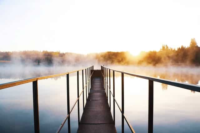 Ponte com rio embaixo e neblina com sol refletindo