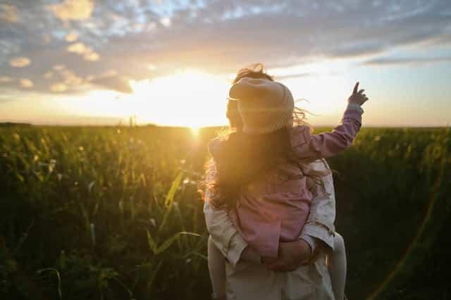 Mãe com filha nas costas olhando campo verde e sol refletindo ao fundo